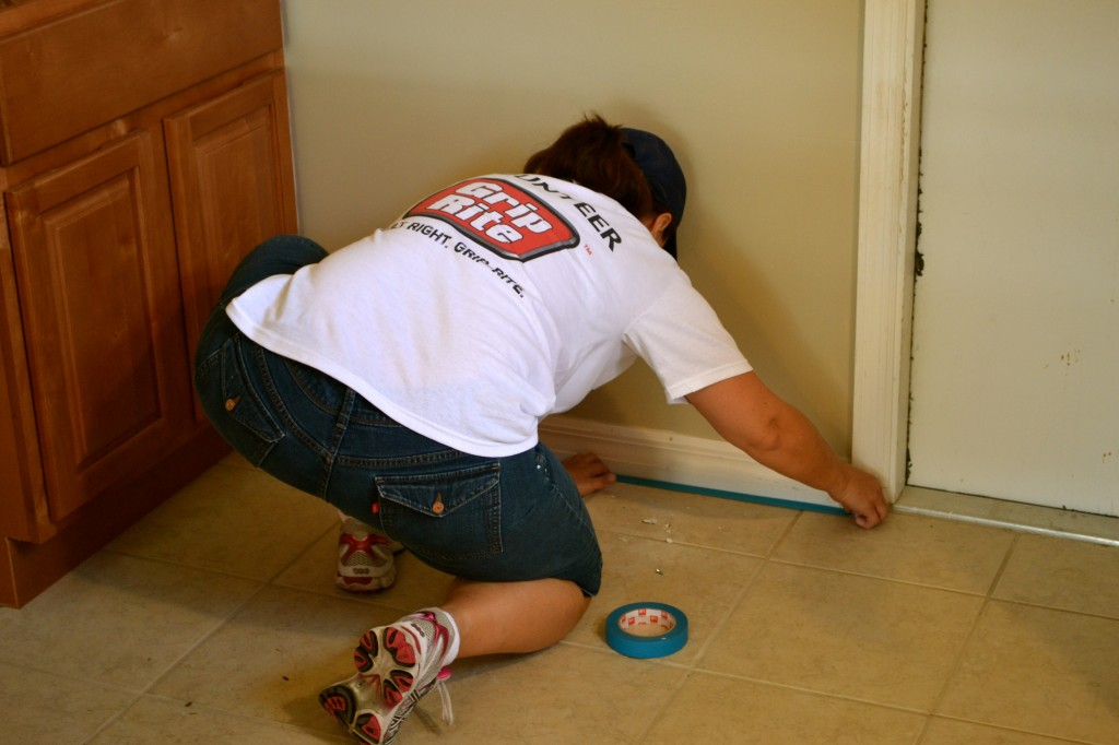 Putting down painters tape in the kitchen.